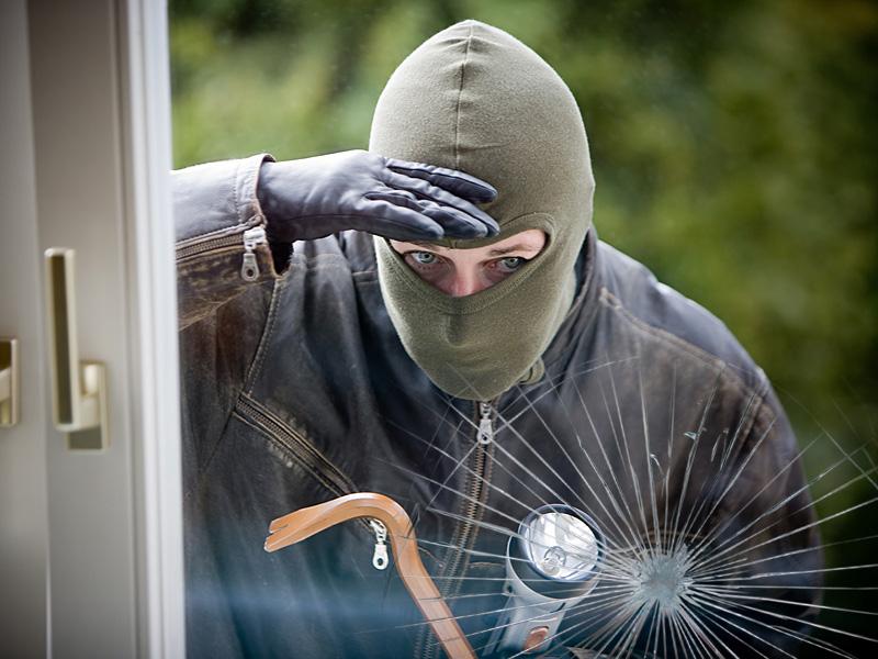 Einbrecher schaut von Außen durch eine Glasscheibe