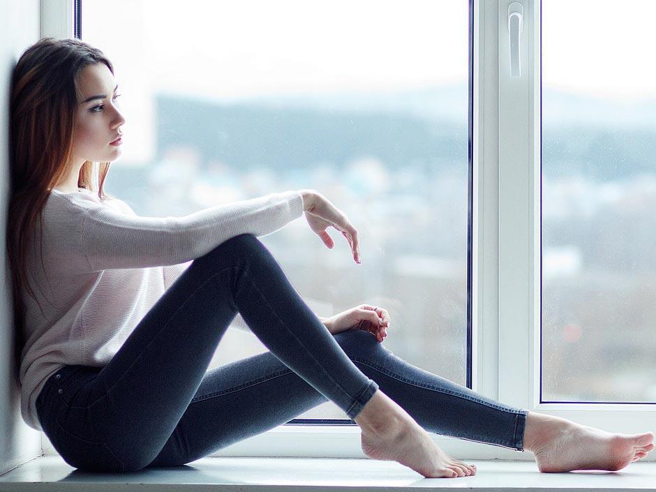 Frau die am Fenster sitzt